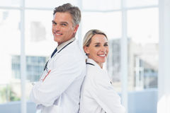 Smiling doctors posing together back to back Royalty Free Stock Images