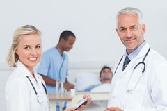 Smiling doctors standing in front of patient Royalty Free Stock Photos