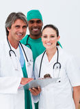 Smiling doctors and surgeon taking notes Stock Images