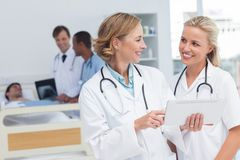 Smiling doctors talking to each other Stock Photos