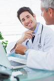 Smiling doctors talking together about something on their laptop Royalty Free Stock Photos