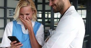 Smiling doctors using smartphone. In hospital hallway stock footage