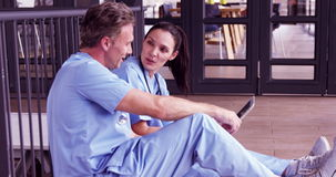 Smiling doctors watching a tablet together. In hospital stock footage
