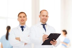 Smiling doctors in white coats with clipboard Royalty Free Stock Image