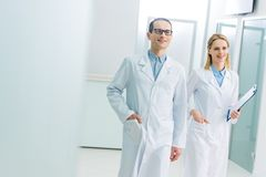 Smiling doctors in white coats with diagnosis. In hospital corridor royalty free stock photography