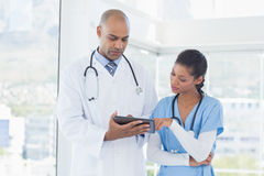Smiling doctors working with tablet together Stock Photo