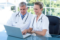 Smiling doctors working together on laptop Stock Photos