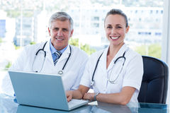 Smiling doctors working together on laptop Stock Photography