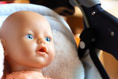 Smiling doll with blue eyes. Cute doll with bright blue eyes in a baby carriage close-up stock image