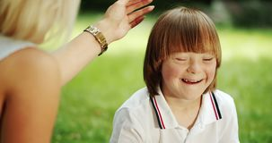 Smiling down syndrome boy and mother in park. Adorable red-haired boy with Down syndrome feeling happy with mother in park, spending time together stock footage