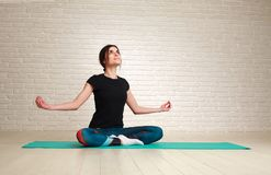Smiling and dreamy woman doing yoga exercises sitting in lotus. Young smiling and dreamy woman doing yoga exercises while sitting in lotus pose Royalty Free Stock Images