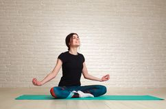 Smiling and dreamy woman doing yoga exercises sitting in lotus. Young smiling and dreamy woman doing yoga exercises while sitting in lotus pose Royalty Free Stock Photo