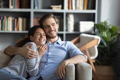 Free Smiling Dreamy Young Couple Hugging, Relaxing On Couch At Home Stock Photo - 188670130
