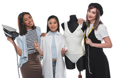 Smiling dressmakers holding tailor tools while working with white bodysuit on dummy Royalty Free Stock Photos