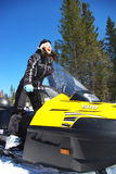 Smiling driver. Young happy woman riding a snowmobile Stock Photos