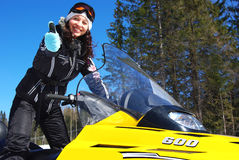 Smiling driver. Young happy woman riding a snowmobile Stock Photo