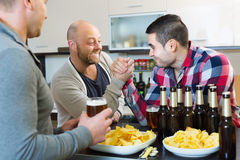 Smiling and drunk men armwrestling Stock Images