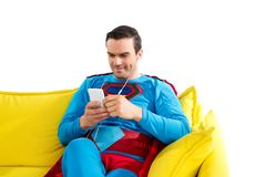 Smiling superman in earphones sitting on sofa and using smartphone. Isolated on white royalty free stock images