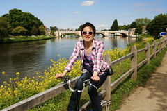 Smiling East Asian Woman with Bicycle on sunny day Stock Photo