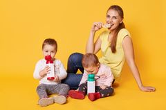 A smiling eating mother takes care of her little funny daughters. Calm adorable babies drink liquid and have relax during their royalty free stock photos