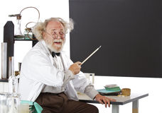 Smiling eccentric  scientist points to blackboard Royalty Free Stock Photography