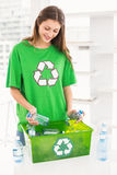 Smiling eco-minded brunette holding recycling bottles Stock Images