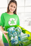 Smiling eco-minded brunette showing recycling box Stock Images