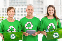 Smiling eco-minded colleagues with recycling boxes Royalty Free Stock Photo