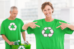Smiling eco-minded woman showing her recycling shirt Royalty Free Stock Images