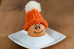 Smiling egg with knitted bonnet sitting in white eggcup Royalty Free Stock Photography