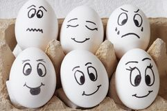 Smiling eggs. White eggs with different faces in a packet Royalty Free Stock Image