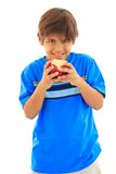 Smiling eight year old boy biting apple Royalty Free Stock Image