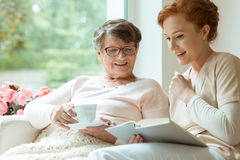 Elder lady during free time. Smiling elder lady with blanket and glasses listening to her nurse reading a book during free time Stock Image