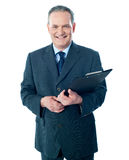 Smiling elderly businessman holding clipboard Royalty Free Stock Photography