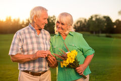 Smiling elderly couple with bouquet. Stock Photo