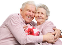 Smiling elderly couple and box with gift. On white background Royalty Free Stock Images