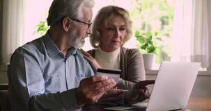 Elderly couple using laptop and credit card buying on internet