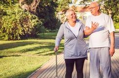 Elderly couple walking through the park stock photography
