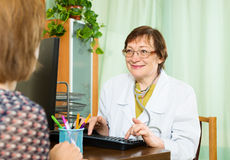 Smiling elderly doctor advises female patient Stock Photo