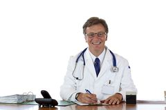 Smiling elderly doctor writes down patient record Stock Photography