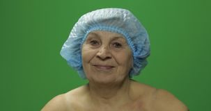 Smiling elderly female in protective hat looking to camera. Plastic surgery stock image