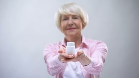 Smiling elderly female showing supplements into camera, health support, vitamins stock video