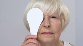 Smiling elderly female squinting on vision examination, closing one eye, health stock footage