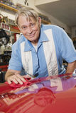 Smiling elderly man cleaning red hood of car in automobile repair shop Stock Photos