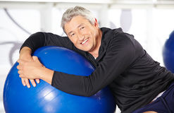Smiling elderly man with exercise. Smiling elderly man sitting with an exercise ball in a gym Royalty Free Stock Image