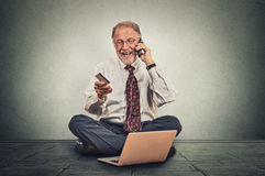 Smiling elderly man making order by mobile phone sitting on a floor of his office Stock Image