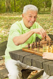 Smiling elderly man playing chess Royalty Free Stock Photo