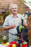 Smiling elderly man. Smiling senior man drinking a glass of wine after harvesting this years rich produce royalty free stock photos