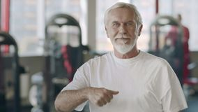 Smiling elderly man showing thumb up gesture in healthy club. stock video
