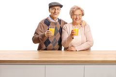 Smiling elderly man and woman holding glasses with orange juice behind a wooden counter royalty free stock photos